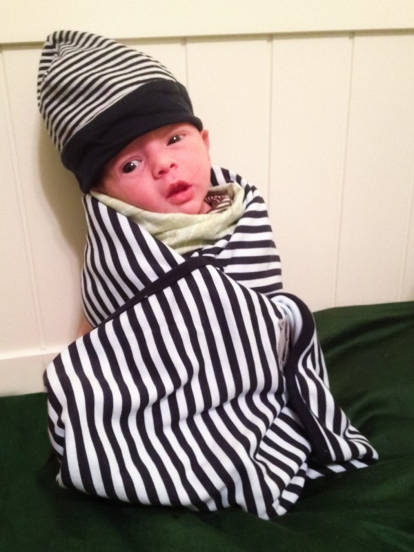 Baby boy Sam propped-up and wrapped in a striped blanket, wearing a striped hat