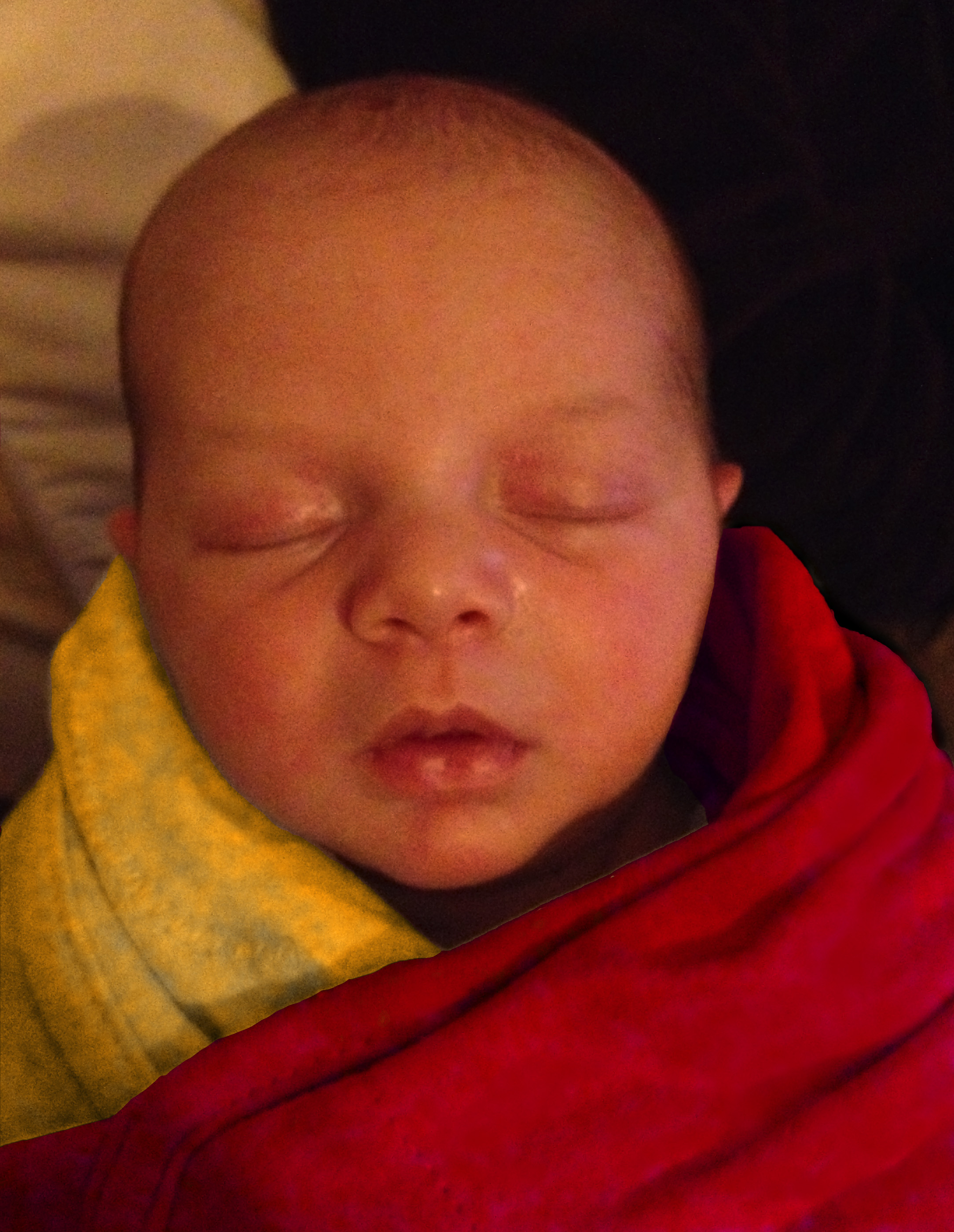 bald baby Sam, swaddled and photoshopped to look like the Dalai Lama in a saffron robe.