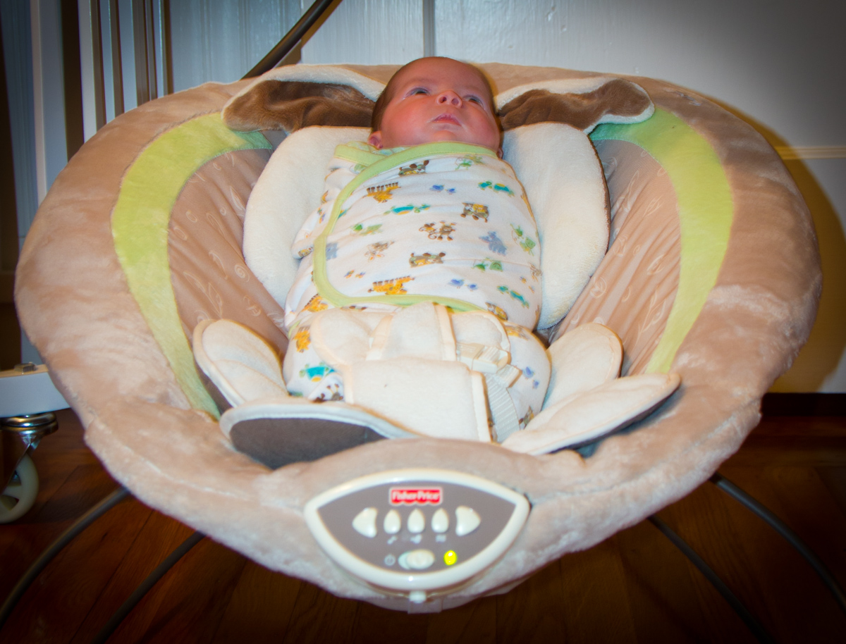Baby boy Max is swaddled and sitting in a bouncy chair.