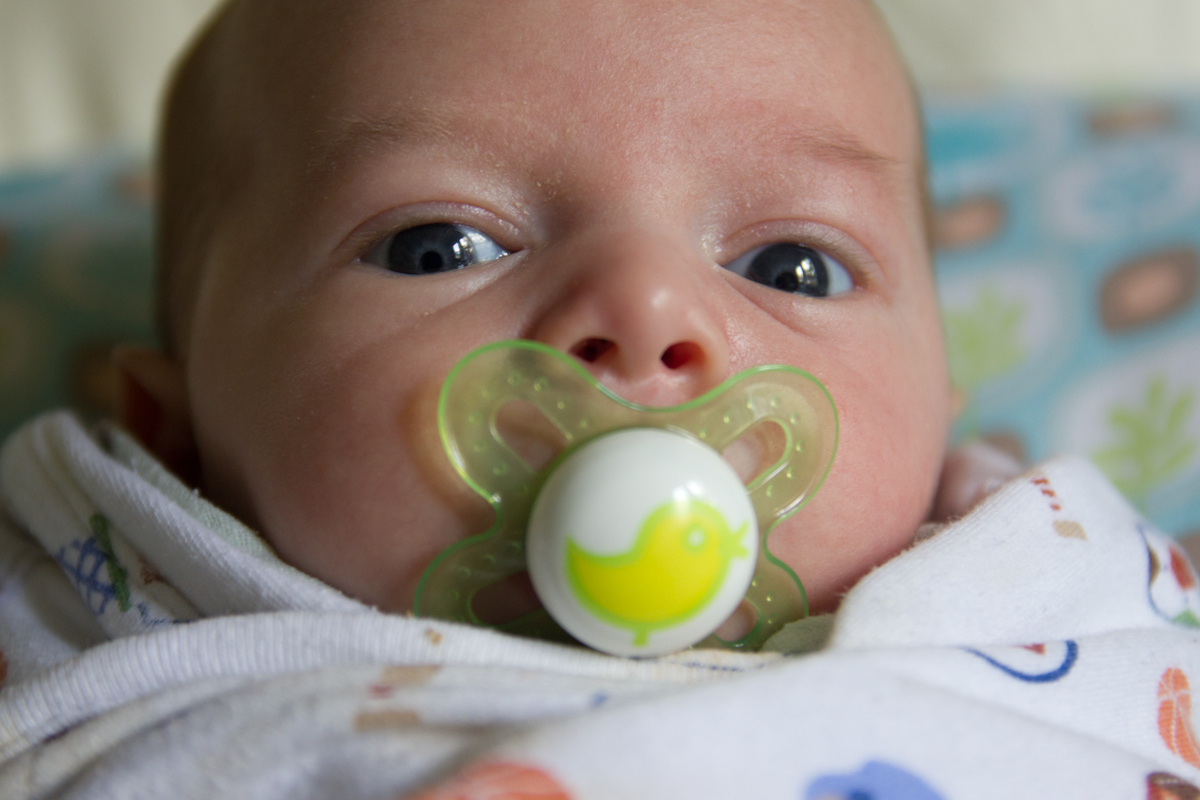 Baby boy Sam with a pacifier in his mouth, looking at the camera. The pacifier has a chick on it.