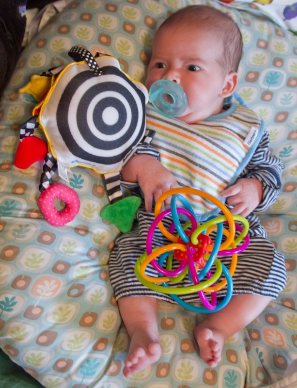 baby boy Max on a Boppy with complex toys, like a Whoozit