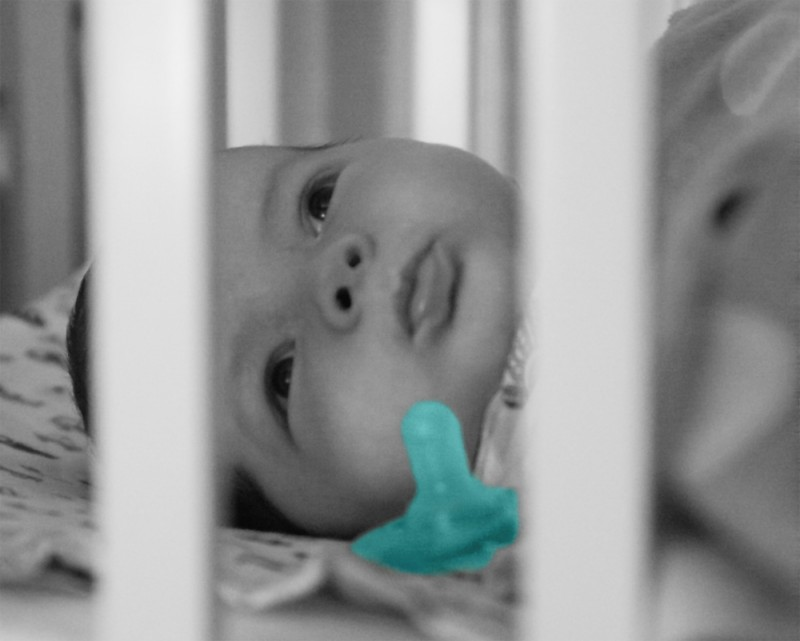 baby boy Max seen through the bars of his BAM bassinet, with a pacifier by his face. The image is grayscale with a colorful blue-green pacifier.