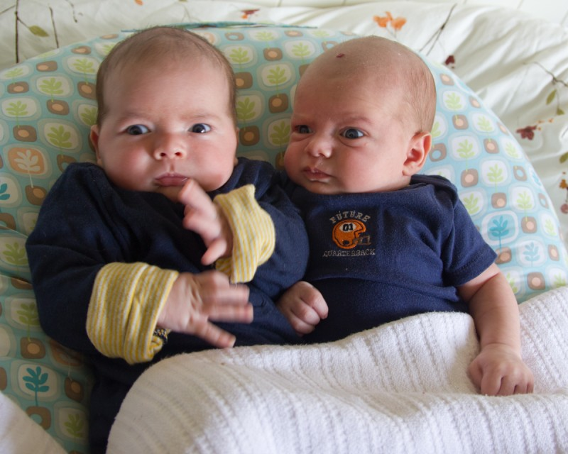 baby boys max and sam, wearing navy blue, conspire on a Boppy Lounger