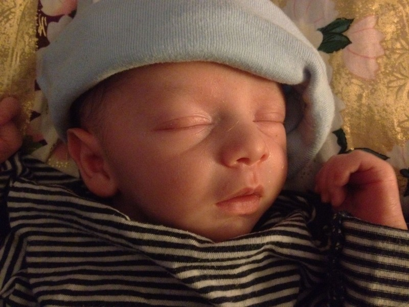 Baby boy Sam, asleep wearing a stripe shirt against a golden pillow. The tilt of his hat makes it look like a French beret.