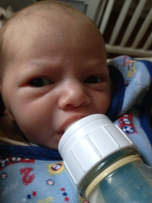baby boy Sam drinking from a bottle, looking a bit perturbed