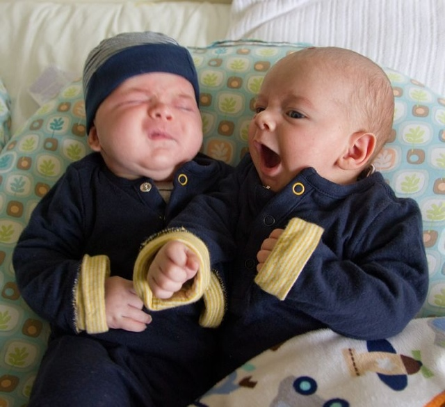 twin baby boys max and sam wearing navy blue gap outfits sit on a Boppy Newborn Lounger. Sam appears to be singing loudly or talking, Max is perhaps listening to music