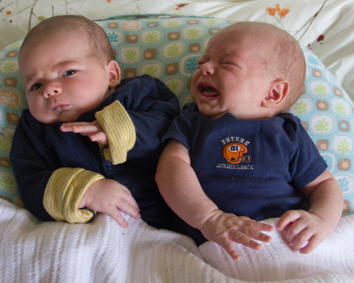 twin baby boys max and sam sit together on a Boppy pillow, both wearing navy blue. sam cries toward max and max recoils