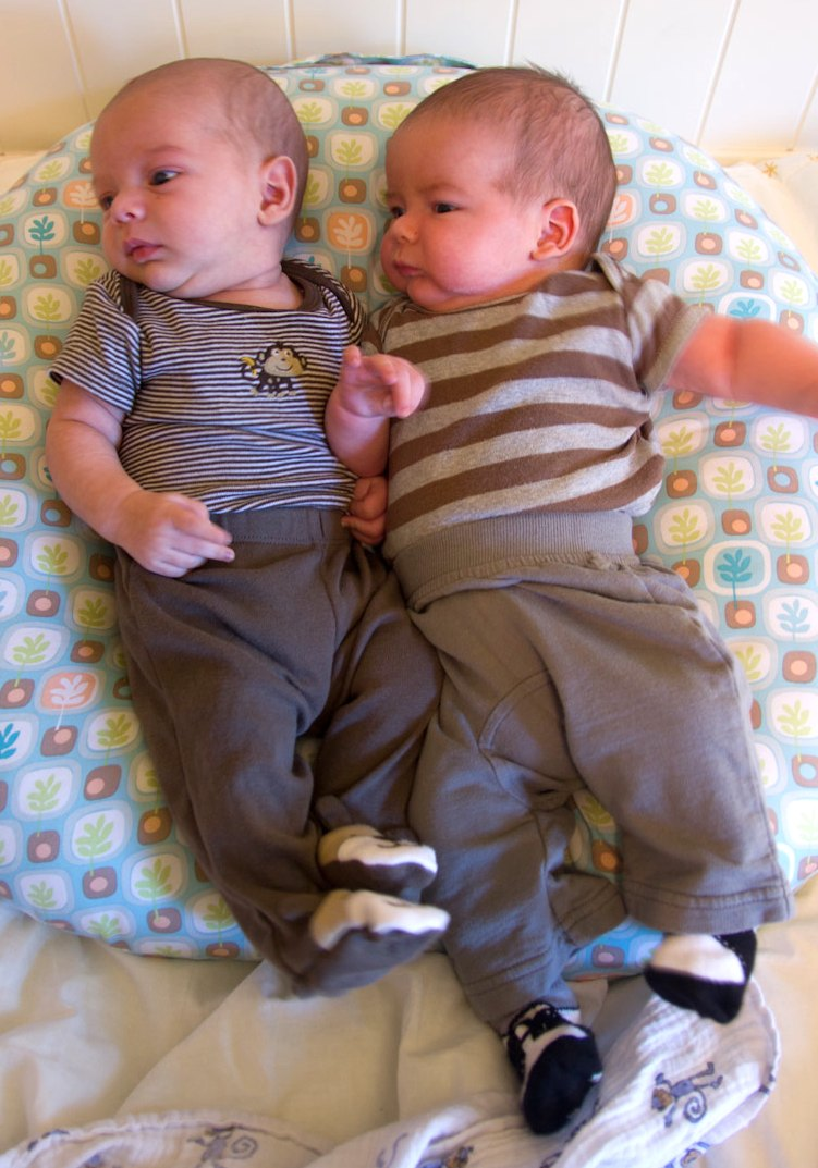 twin brothers, baby boys sam and max sit on a Boppy Newborn Lounger. Both are wearing pants and onesies.