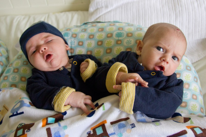 twin baby boys, max and sam, wearing matching navy blue Gap clothes sing an opera aria duet while sitting on a Boppy Baby Lounger