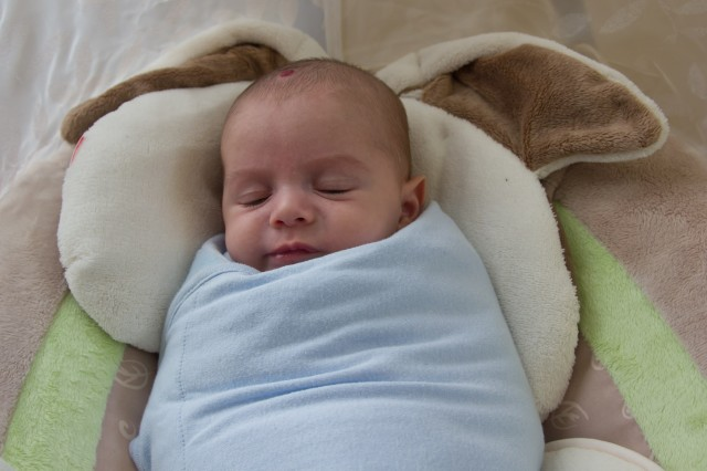 baby boy sam sleeps in a light blue Summer SwaddleMe blanket, sitting in a Fisher Price My Little Snugabunny Cradle and Swing