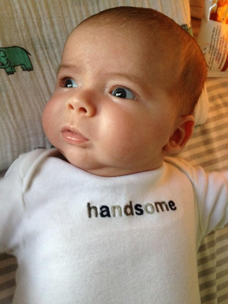 baby boy max wearing a white onesie that says 'handsome'