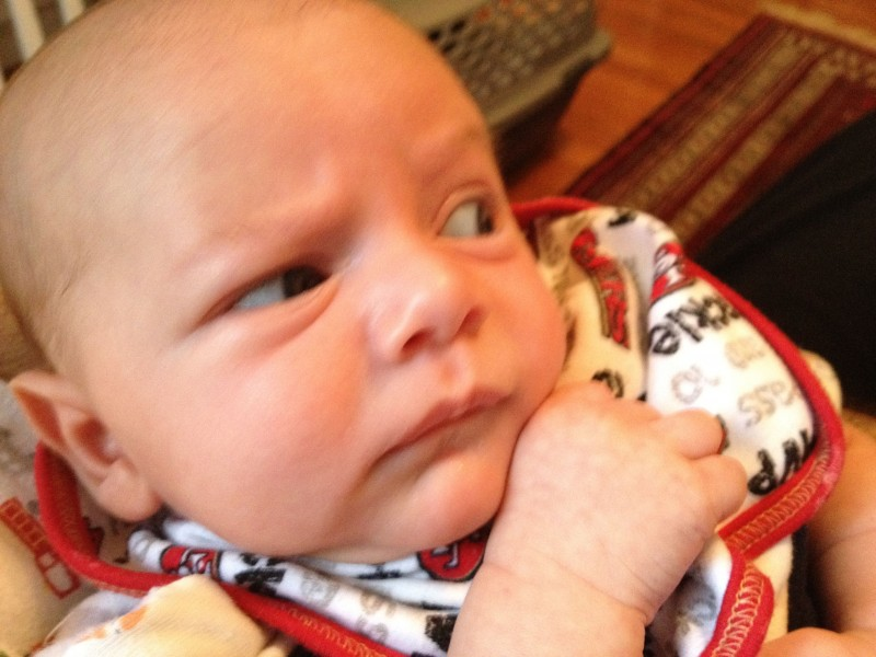 baby boy sam, close-up, draws his closed fist close to his chin