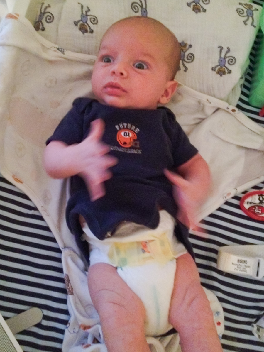 baby boy sam wearing a navy blue onesie and a diaper looks surprised to be on the changing table