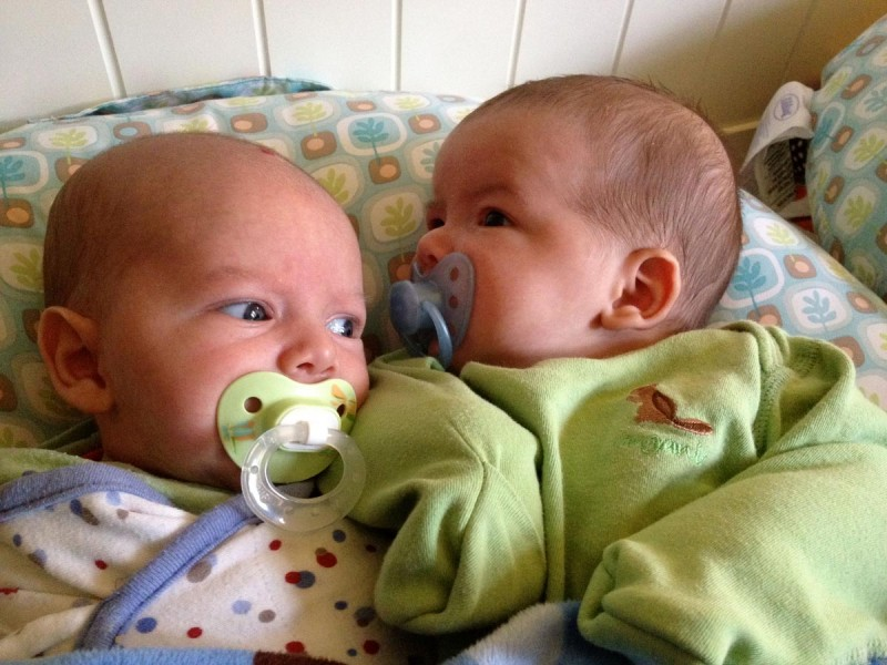 baby boys, twin brothers, sam and max, sit on a Boppy Newborn Lounger with pacifiers. Sam is swaddled, max is wearing a sweat-pea suit