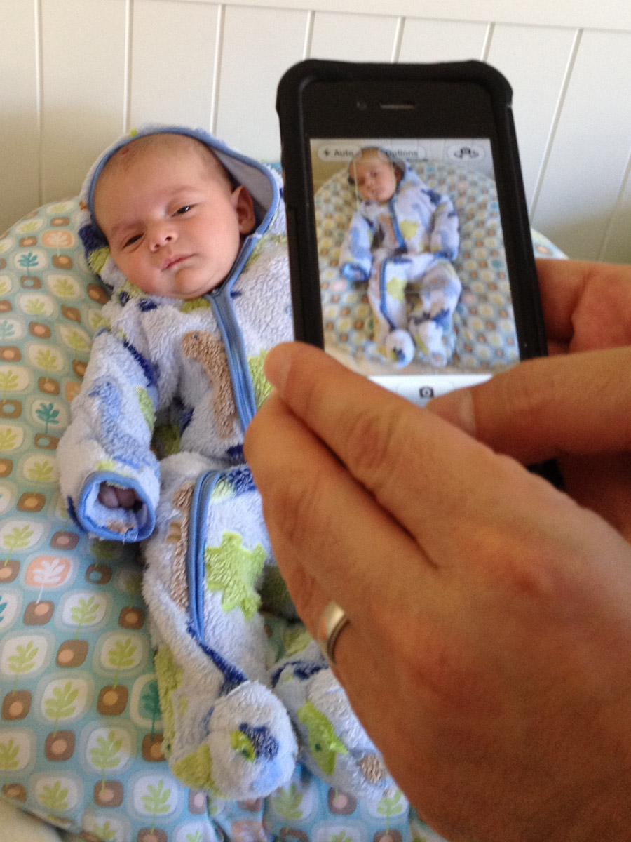 baby boy sam sits wearing a zip-up suit while his father takes a photo of him with an iPhone. The photo, taken with an iPhone, is of a photo being taken with an iPhone