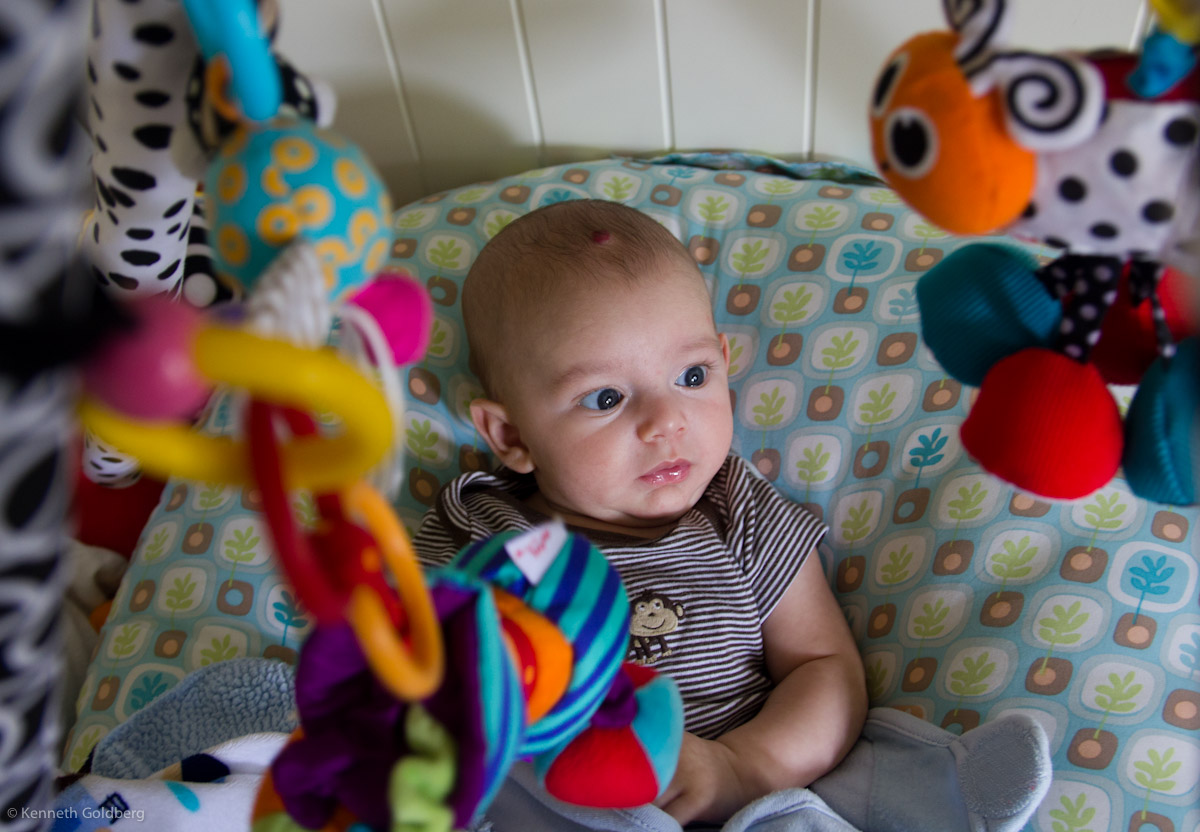 baby boy sam sits on a Boppy Newborn Lounger surrounded by many hanging toys