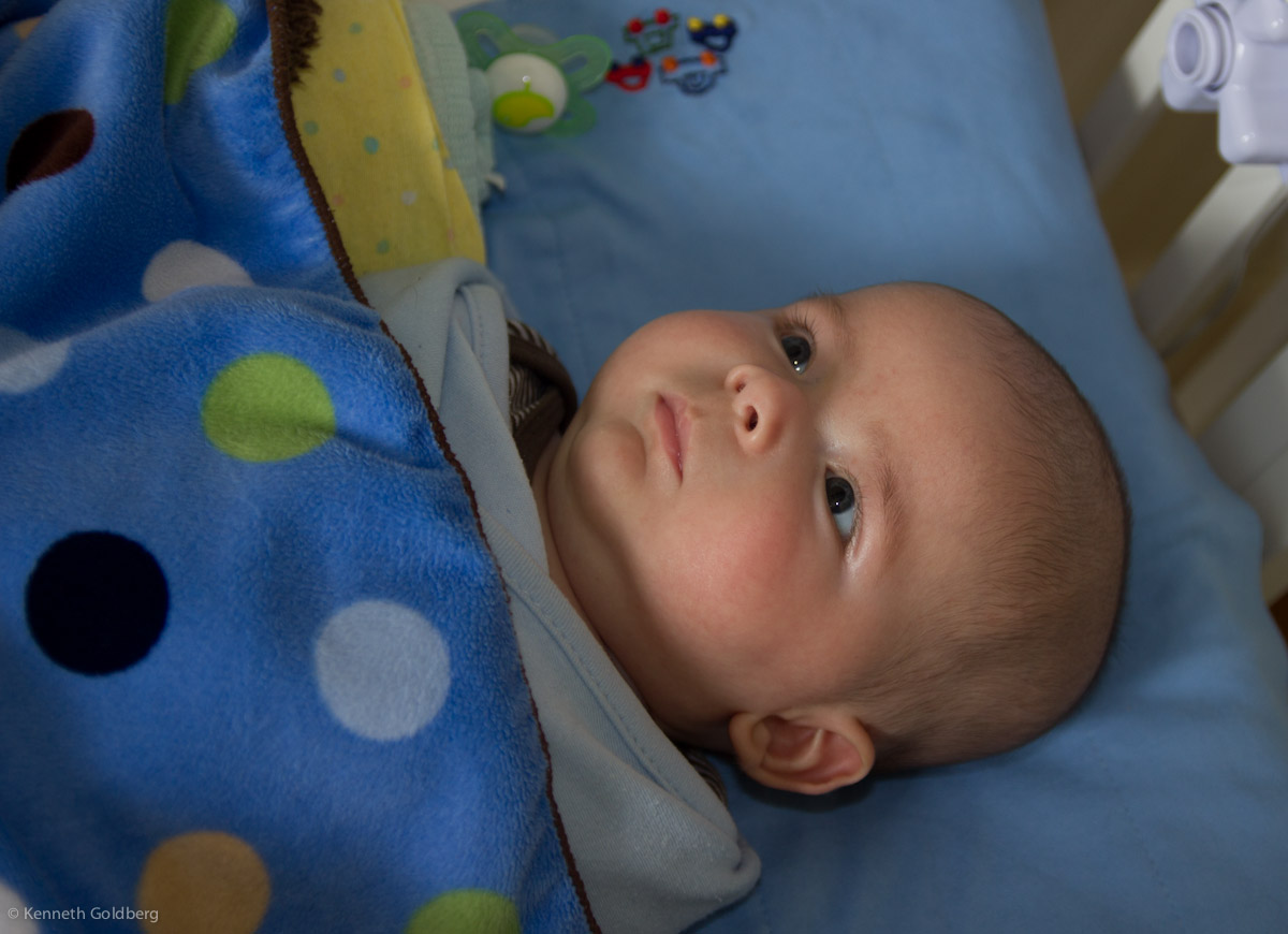 baby boy max lies awake in his crib, staring upward thoughtfully