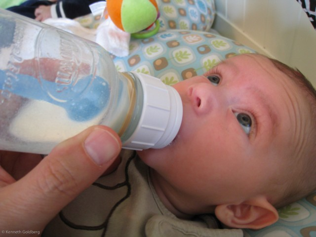 baby boy sam drinks milk from a Dr. Brown's bottle