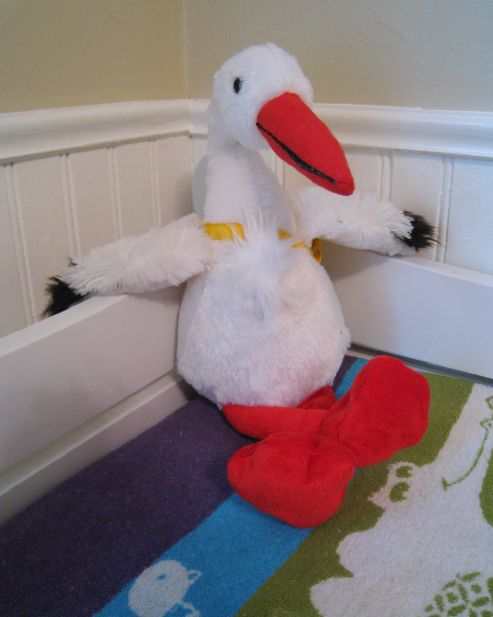 a stuffed stork sits smugly in the corner of a changing table