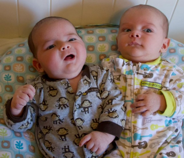 baby boys , fraternal twin brothers, max and sam, sit on a Boppy Newborn Lounger. Max is talking to Sam. It looks like he's telling the punchline of a good joke.