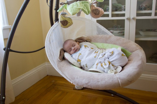 baby boy sam swings in a Fisher Price My Little Snugabunny Cradle 'n Swing