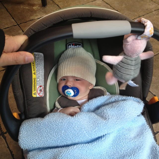baby boy max sits in a Chicco car seat, with a pacifier in his mouth and his knit cap rolled out surfer-style. Piglet hangs from above.
