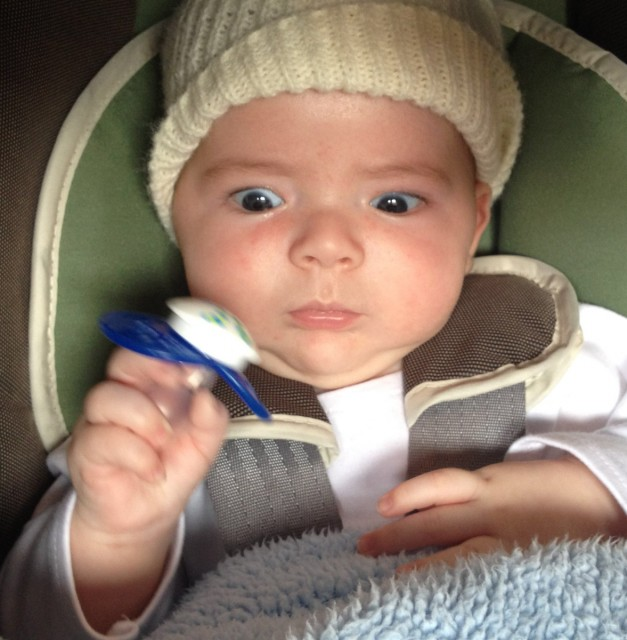 baby boy max sitting in a Chicco car seat and wearing a knit cap, holds onto a pacifier that he has removed from his mouth and he stares at it with great focus