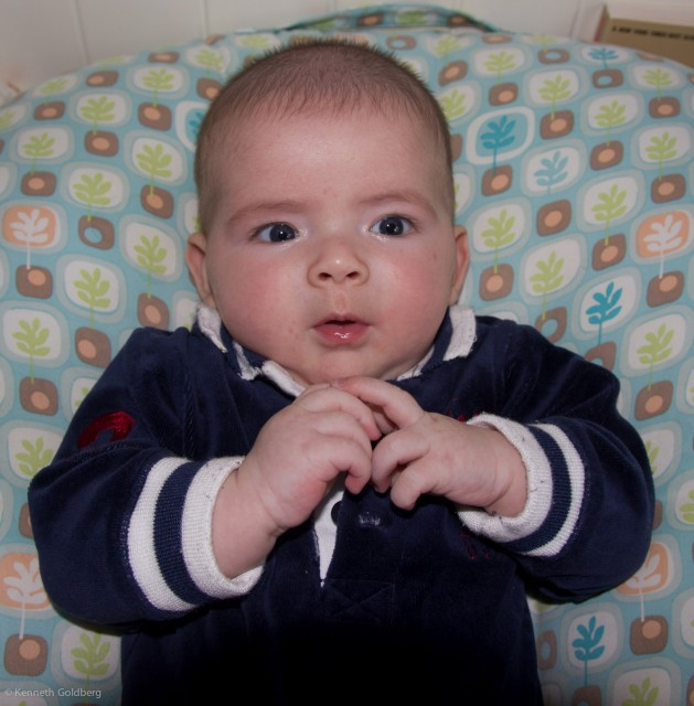 Baby boy max, wearing a black Polo outfit, sits on a BoppyNewbornLounger, while giving insight to his father