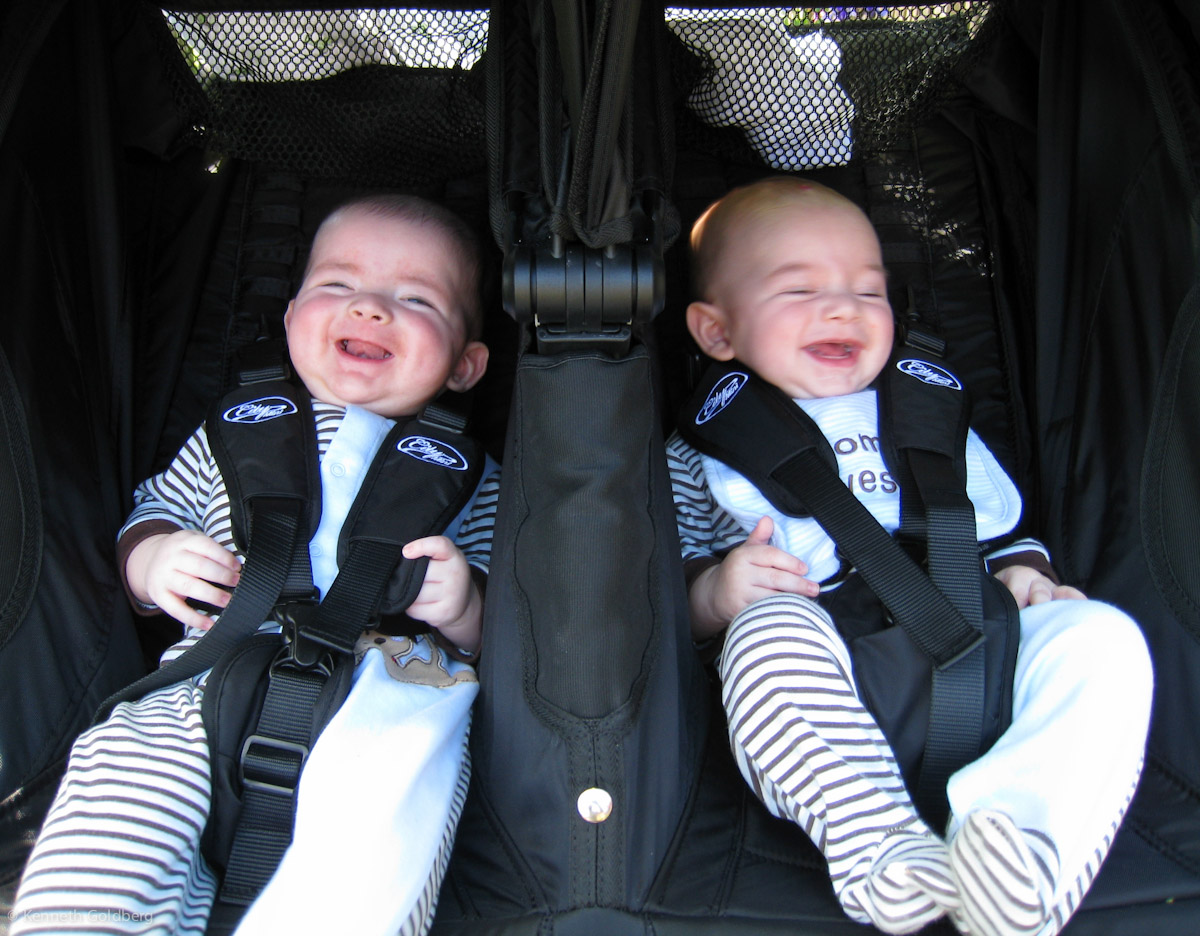 twin brothers max and sam laugh while strapped into a city mini GT double stroller
