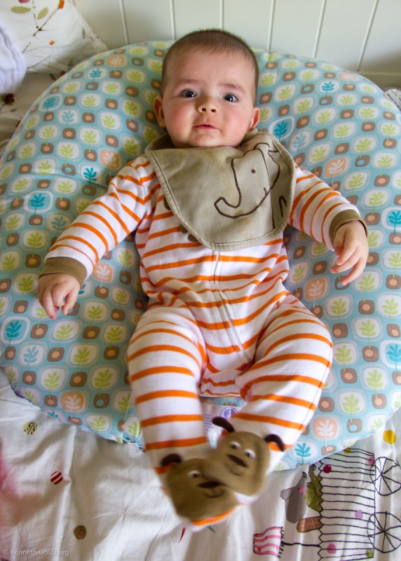 baby boy max sits on a Boppy Newborn Lounger wearing an orange striped suit and an elephant bib