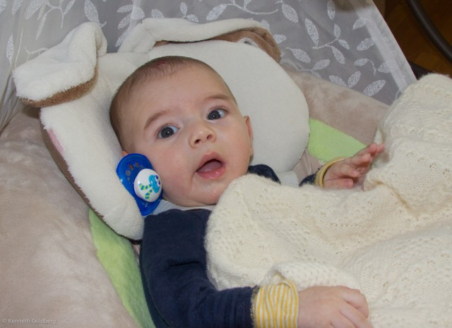 baby boy sam, sitting in a My Little Snugabunny Cradle'N'Swing, has a blue pacifier stuck next to his face