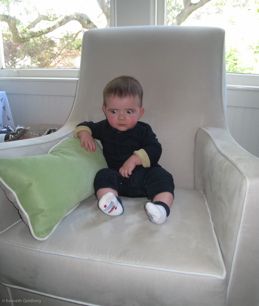 baby boy max sits in a big chair, looking serious