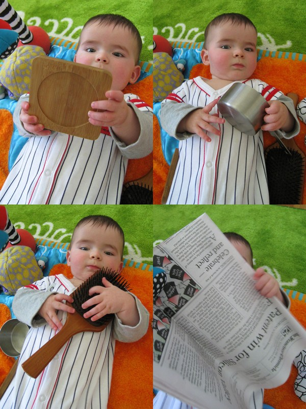 baby boy max with a bamboo coaster, a stainless steel measuring cup, a wooden hairbrush, and The San Francisco Chronicle newspaper