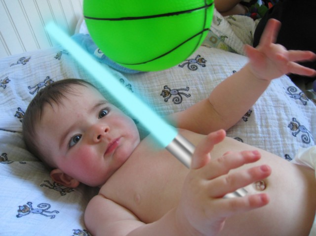 baby box max holds a light saber battling a green ball