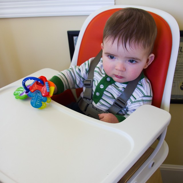 baby boy max, holding a set of colorful keys, presides over the high chair