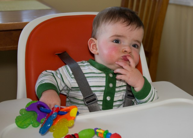 baby boy max sits in a highchair thinking deeply
