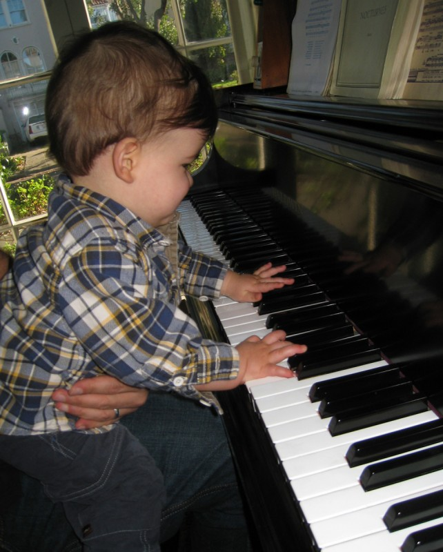 baby boy max sits at the piano and plays