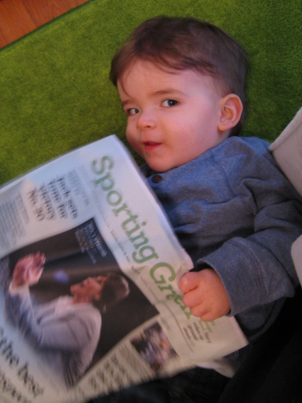 baby boy max looks coy as he read the San Francisco Chronicle Sporting Green