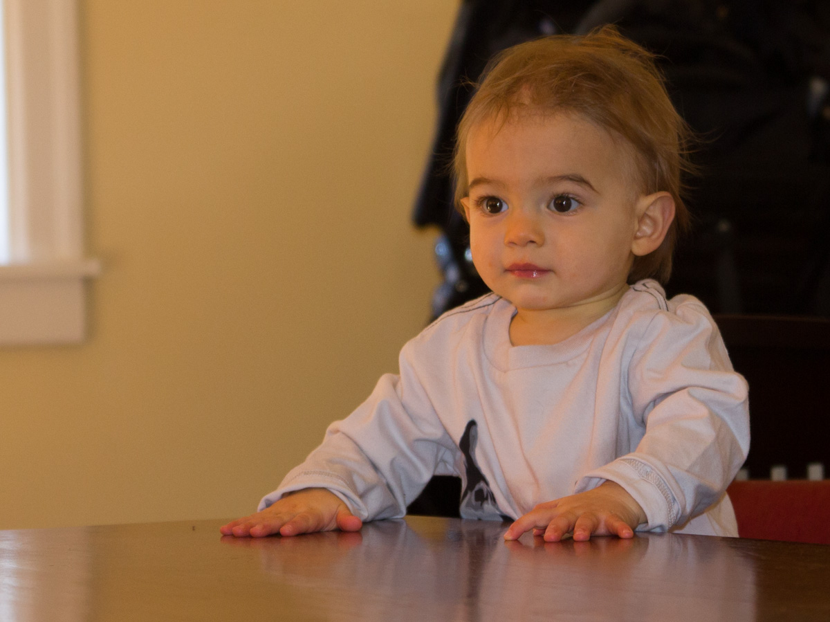 Baby boy Sam stands at the coffee table